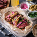 Michelada Marinated Steak Tacos with Chipotle Avocado Sauce and Beer Pickled Onions